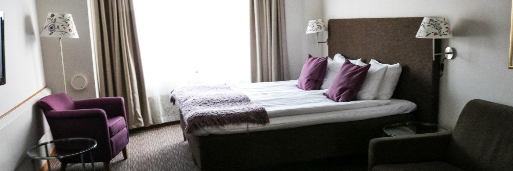 Dubbelsäng och fåtöljer i  ett rum på Mora Hotell