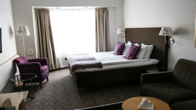Dubbelsäng med fåtöljer och bord i ett rum på Mora Hotell